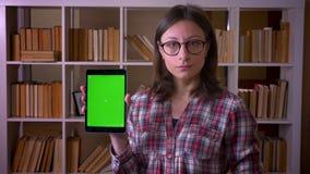 Close-upspruit van jonge aantrekkelijke vrouwelijke student in glazen gebruikend de tablet en tonend het groene scherm aan camera stock videobeelden