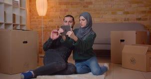 Close-upspruit van jonge gelukkige moslimpaarzitting op de vloer naast de dozen in onlangs het gekochte flat gebruiken stock videobeelden
