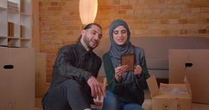 Close-upspruit van jonge gelukkige moslimpaarzitting op de vloer naast de dozen in onlangs het gekochte flat glimlachen stock videobeelden
