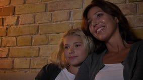 Close-upspruit van jonge Kaukasische moeder en een meisje die op TV letten terwijl het zitten bij bank en het koesteren Mamma die stock videobeelden