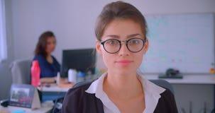 Close-upspruit van jonge Kaukasische onderneemster die in glazen camera bekijken die cheerfully in het bureau binnen glimlachen stock video