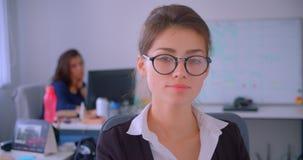 Close-upspruit van jonge Kaukasische onderneemster die in glazen camera bekijken die gelukkig in het bureau binnen glimlachen met stock footage