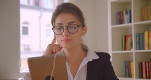 Close-upspruit van jonge Kaukasische onderneemster in glazen en vibes het doorbladeren op de tablet en het luisteren aan muziek i stock video