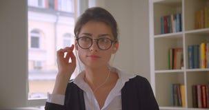 Close-upspruit van jonge Kaukasische onderneemster in glazen en vibes het doorbladeren op de tablet en het luisteren aan muziek i stock footage