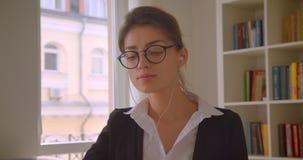 Close-upspruit van jonge Kaukasische onderneemster in glazen en vibes het doorbladeren op de tablet en het luisteren aan muziek m stock footage