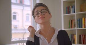 Close-upspruit van jonge Kaukasische onderneemster in glazen en vibes het gebruiken van de tablet en het luisteren aan muziek het stock video