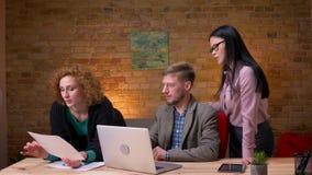 Close-upspruit van jonge Kaukasische zakenman die aan laptop werkt en gegevens bespreekt met twee vrouwelijke werknemers E stock video