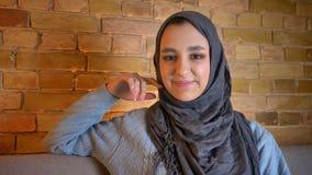 Close-upspruit van jonge leuke moslim vrouwelijke tiener die in hijab recht camera bekijken die cheerfully binnen glimlachen bij stock video