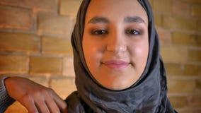 Close-upspruit van jonge leuke moslim vrouwelijke tiener die in hijab recht camera bekijken die gelukkig binnen bij comfortabel g stock videobeelden
