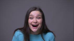 Close-upspruit van jonge vrij donkerbruine vrouwelijke die het glimlachen wordt opgewekt bekijkend camera met achtergrond op grij stock videobeelden