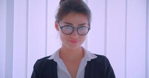 Close-upspruit van jonge vrij Kaukasische businesswomanand die haar glazen bevestigen en camera bekijken die cheerfully glimlache stock footage