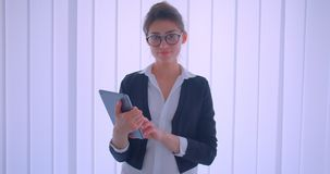 Close-upspruit van jonge vrij Kaukasische onderneemster die een tablet houden en camera binnen in een witte ruimte bekijken stock video