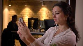 Close-upspruit van jonge vrij Kaukasische onderneemster die selfies op de telefoon nemen terwijl het zitten voor laptop royalty-vrije stock afbeelding