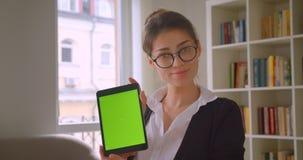 Close-upspruit van jonge vrij Kaukasische onderneemster in glazen gebruikend de tablet en tonend groene chroma het zeer belangrij stock videobeelden