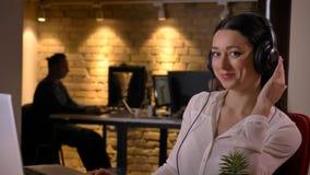 Close-upspruit van jonge vrij Kaukasische onderneemster in hoofdtelefoons die op laptop typen en camera het glimlachen bekijken royalty-vrije stock fotografie