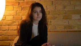 Close-upspruit van jonge vrij Kaukasische vrouwelijke het letten op TV zorgvuldig terwijl het zitten op de laag royalty-vrije stock fotografie
