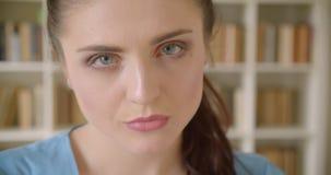 Close-upspruit van jonge vrij Kaukasische vrouwelijke student die camera met boekenrekken op de achtergrond in bekijken stock videobeelden