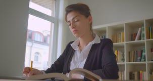 Close-upspruit van jonge vrij Kaukasische vrouwelijke student die nota's in de universitaire bibliotheek nemen stock videobeelden