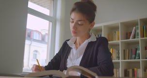 Close-upspruit van jonge vrij Kaukasische vrouwelijke student die nota's in de universiteitsbibliotheek nemen stock videobeelden