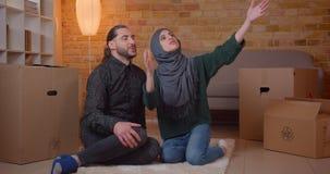 Close-upspruit van jonge vrolijke moslimpaarzitting op de vloer naast de dozen in een onlangs gekochte flat stock videobeelden