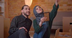 Close-upspruit van jonge vrolijke moslimpaarzitting op de vloer naast de dozen in onlangs het gekochte flat glimlachen stock footage