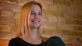 Close-upspruit van jonge vrouwelijke student die op een film op TV letten die met opwinding glimlachen terwijl binnen het zitten  stock footage