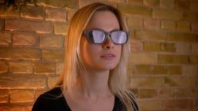 Close-upspruit van jonge vrouwelijke tiener die op een 3D verschrikkingsfilm in glazen op TV letten en een jumpscare krijgen terw stock videobeelden