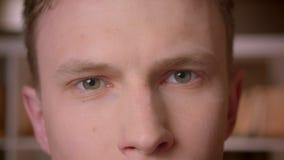 Close-upspruit van jonge zekere Kaukasische mannelijke student die camera in de universiteitsbibliotheek bekijken stock videobeelden