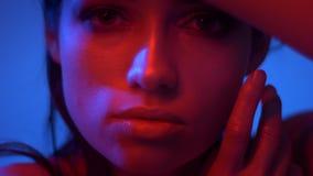 Close-upspruit van mannequin in rode en blauwe neonlichten die haar gezicht met vingers en horloges verbergen in camera stock footage