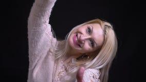 Close-upspruit van midden oud Kaukasisch blondewijfje die duimen tonen terwijl het glimlachen van cheerully het bekijken camera stock videobeelden