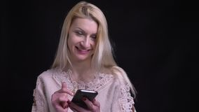Close-upspruit van midden oud Kaukasisch blondewijfje die op de telefoon doorbladeren die en camera lachen bekijken stock videobeelden