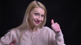 Close-upspruit van midden oud Kaukasisch duimen tonen en wijfje die terwijl recht het bekijken camera glimlachen stock videobeelden