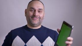 Close-upspruit van midden oud Kaukasisch mannetje die op laptop doorbladeren en het groene chromascherm tonen aan camera het glim stock footage