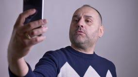 Close-upspruit van midden oud Kaukasisch mannetje die selfies op de telefoon nemen en verschillende faciauitdrukkingen maken stock video