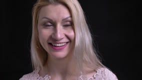 Close-upspruit van midden oud Kaukasisch recht camera bekijken en wijfje die cheerfully glimlachen stock footage