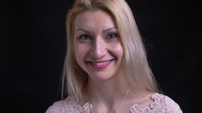 Close-upspruit van midden oud Kaukasisch wijfje met leuk en blondehaar die gelukkig terwijl het bekijken camera zijn glimlachen stock video