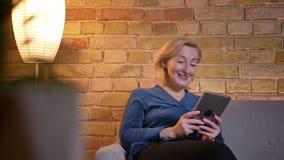Close-upspruit van op de tablet doorbladeren en eldery Kaukasisch wijfje die opgewekt terwijl binnen het zitten op de laag worden stock videobeelden