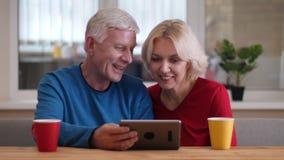 Close-upspruit van oud gelukkig paar die een videogesprek hebben de tablet met koppen met thee op het bureau binnen in comfortabe stock footage