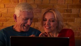 Close-upspruit van oud gelukkig paar die op een film op de laptop zitting op de laag binnen in een comfortabele flat letten stock footage