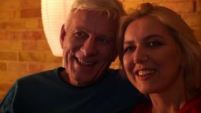 Close-upspruit van oud gelukkig paar die TV-op het glimlachen letten rustend op de bank binnen in een comfortabele flat stock videobeelden