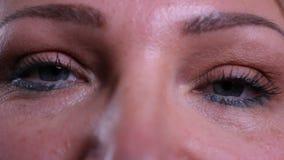 Close-upspruit van oud Kaukasisch vrouwelijk gezicht met ogen die camera bekijken stock video