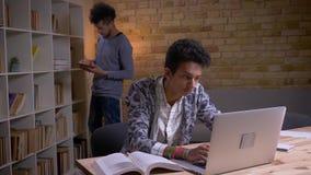Close-upspruit van twee cultureel diverse studenten die in de bibliotheek binnen leren Indisch mannetje die online op bestuderen stock videobeelden