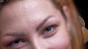 Close-upspruit van volwassen aantrekkelijk blonde Kaukasisch vrouwelijk gezicht met haar ogen die seductively camera met bokeh be stock footage