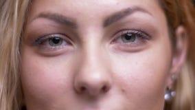 Close-upspruit van volwassen aantrekkelijk blonde Kaukasisch vrouwelijk gezicht met ogen die en openings en kijkend recht worden  stock footage