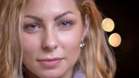 Close-upspruit van volwassen aantrekkelijk blonde Kaukasisch wijfje die recht camera bekijken en cheerfully met bokeh glimlachen stock videobeelden
