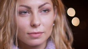 Close-upspruit van volwassen aantrekkelijk blonde Kaukasisch wijfje die recht camera met bokehachtergrond bekijken stock video