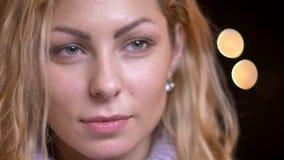 Close-upspruit van volwassen aantrekkelijk blonde Kaukasisch wijfje die recht camera met bokehlichten bekijken op de achtergrond stock videobeelden