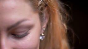 Close-upspruit van volwassen aantrekkelijk blonde Kaukasisch wijfje die seductively en voor de camera stellen kijken stock video