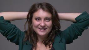 Close-upspruit van volwassen aantrekkelijk donkerbruin en gelukkig wijfje die werpend haar haar die camera bekijken met worden op stock video