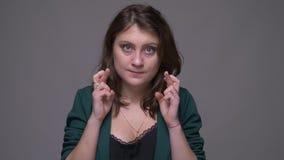 Close-upspruit van volwassen aantrekkelijk donkerbruin haar gekruiste vingers hebben en wijfje die het bezorgde bekijken camera m stock video
